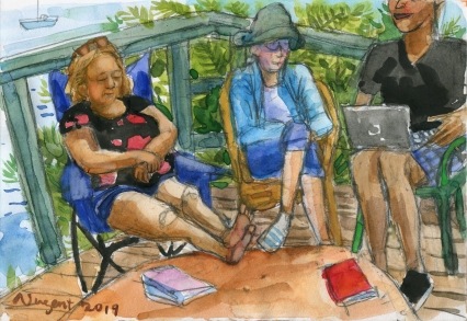 Authors Lori Sherritt, Nan Gregory and Mark David Smith sitting on deck with ocean view behind them as they share their weekend writing.